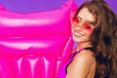 Retrato del primer de la muchacha con el pelo rizado largo en gafas de sol rosadas en fondo púrpura con el colchón rosado cerca e imágenes de archivo libres de regalías