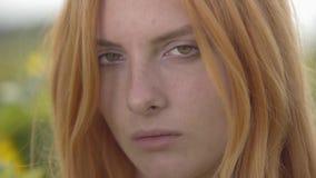 Retrato del primer de la muchacha confiada joven con el pelo rojo y los ojos verdes que miran la cámara al aire libre Concepto de almacen de metraje de vídeo