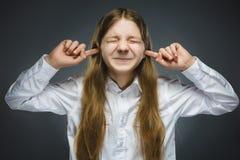 Retrato del primer de la muchacha de griterío que cubre sus oídos, observando No oiga nada Emociones humanas, expresiones faciale Imagen de archivo