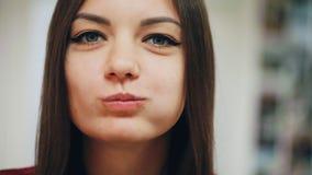 Retrato del primer de la muchacha feliz hermosa que come un buñuelo, gozando de un bocado en el trabajo metrajes