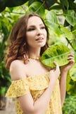 Retrato del primer de la muchacha hermosa joven con el vestido del verano del pelo rizado en bosque tropical Imagen de archivo libre de regalías