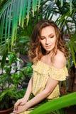Retrato del primer de la muchacha hermosa joven con el vestido del verano del pelo rizado en bosque tropical Imágenes de archivo libres de regalías