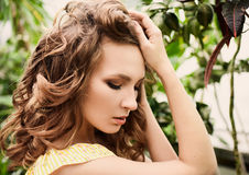 Retrato del primer de la muchacha hermosa joven con el vestido del verano del pelo rizado en bosque tropical Fotos de archivo
