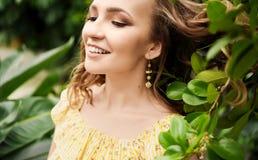 Retrato del primer de la muchacha hermosa joven con el vestido del verano del pelo rizado en bosque tropical Foto de archivo libre de regalías