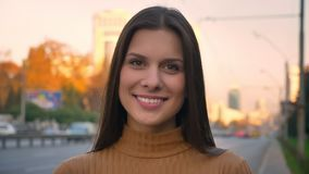 Retrato del primer de la muchacha morena atractiva que da vuelta a la cámara con sonrisa sincera en fondo del camino metrajes