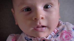 Retrato del primer de la muchacha recién nacida bonita que miente en el sofá y que mira en cámara alegre con sonrisa linda metrajes