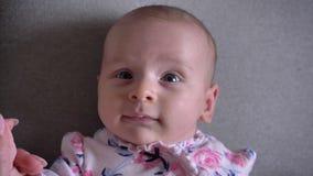 Retrato del primer de la muchacha recién nacida bonita que mira en cámara alegre con sonrisa linda y que grita almacen de video