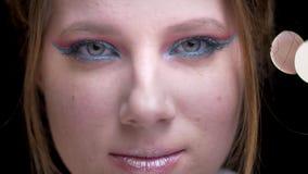 Retrato del primer de la muchacha rubia caucásica con maquillaje colorido brillante que mira tranquilamente en fondo borroso de l almacen de metraje de vídeo