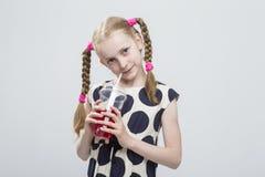 Retrato del primer de la muchacha rubia caucásica hermosa con las coletas que presentan en la polca Dot Dress Against White Imagenes de archivo