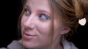 Retrato del primer de la muchacha rubia con el maquillaje colorido que mira alrededor juguetónamente en fondo borroso de las luce metrajes
