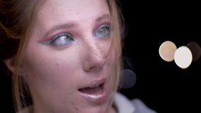 Retrato del primer de la muchacha rubia con el maquillaje colorido que sopla su pelo de la cara alegre en fondo borroso de las lu almacen de video