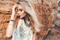Retrato del primer de la muchacha rubia con el pelo largo que presenta a la c?mara en el fondo de piedra Ella lleva el vestido bl imágenes de archivo libres de regalías