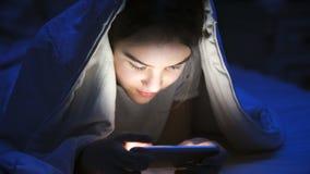 Retrato del primer de la muchacha sonriente con el teléfono móvil debajo de la manta en la noche Imagen de archivo