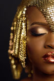 Retrato del primer de la mujer americana africana o negra con el ojo cerrado, el maquillaje creativo y accesorios de oro Imagen de archivo
