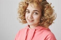 Retrato del primer de la mujer apuesta linda con la situación del pelo rizado mitad-dada vuelta y que echa un vistazo en la cámar Imágenes de archivo libres de regalías