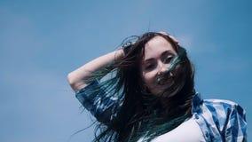 Retrato del primer de la mujer atractiva encantadora que mira la cámara fuera de la luz soleada del día de verano en el fondo ale metrajes