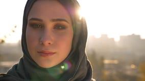 Retrato del primer de la mujer atractiva joven en cabeza de torneado del hijab de la izquierda y de mirar la cámara con confianza almacen de video