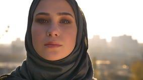 Retrato del primer de la mujer atractiva joven en el hijab que mira con confianza derecho la cámara almacen de video