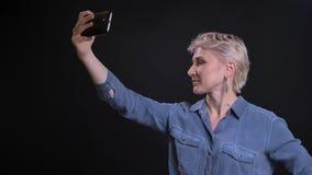 Retrato del primer de la mujer caucásica atractiva que toma selfies en el teléfono que sonríe y que presenta almacen de metraje de vídeo