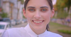 Retrato del primer de la mujer caucásica bonita joven que mira la cámara que sonríe alegre descansando con el disfrute en parque metrajes