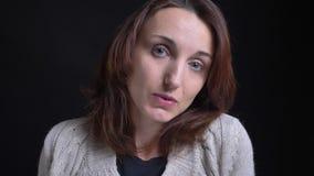 Retrato del primer de la mujer caucásica morena de mediana edad que cabecea aprobado en cámara en fondo negro almacen de metraje de vídeo