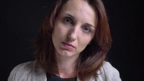 Retrato del primer de la mujer caucásica morena de mediana edad que cabecea aprobado y tranquilamente en cámara en fondo negro almacen de video