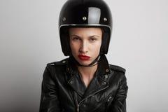 Retrato del primer de la mujer del motorista sobre el fondo blanco, el casco juguetón negro elegante que lleva y la chaqueta de c Fotos de archivo libres de regalías