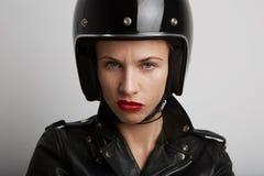 Retrato del primer de la mujer del motorista sobre el fondo blanco, el casco juguetón negro elegante que lleva y la chaqueta de c Fotos de archivo