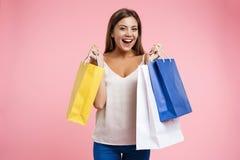 Retrato del primer de la mujer feliz joven que sostiene bolsos en las compras Fotografía de archivo libre de regalías