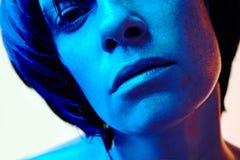 Retrato del primer de la mujer hermosa con el pelo negro corto y la luz azul Imágenes de archivo libres de regalías