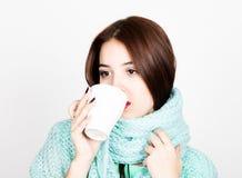 Retrato del primer de la mujer hermosa en una bufanda de lana, un té caliente de consumición o un café de la taza blanca Imagenes de archivo