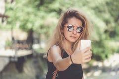 Retrato del primer de la mujer hermosa joven en gafas de sol con el pelo rizado rubio largo que hace las fotos del selfie Imagenes de archivo