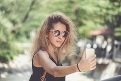 Retrato del primer de la mujer hermosa joven en gafas de sol con el pelo rizado rubio largo que hace las fotos del selfie Fotografía de archivo