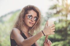 Retrato del primer de la mujer hermosa joven en gafas de sol con el pelo rizado rubio largo que hace las fotos del selfie Imagen de archivo