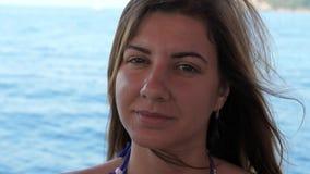 Retrato del primer de la mujer joven bronceada cara linda que flota en un barco en el mar almacen de metraje de vídeo
