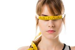 retrato del primer de la mujer joven con la cinta métrica atada alrededor de sus ojos foto de archivo