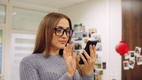Retrato del primer de la mujer joven en smartphone del uso de los vidrios en la oficina Mensaje de texto, en línea practicando su almacen de metraje de vídeo