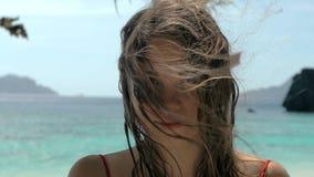 Retrato del primer de la mujer joven europea hermosa que mira en la cámara, pelo que sopla en viento en la playa tropical, azul almacen de video