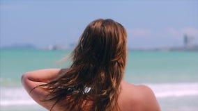 Retrato del primer de la mujer joven de la morenita linda hermosa europea o de la muchacha alegre que mira hacia el mar, corriend almacen de video