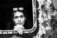 Retrato del primer de la mujer joven que mira hacia fuera la ventana de una vieja instalación industrial Fotos de archivo