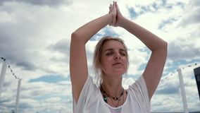 Retrato del primer de la mujer joven de la yogui que hace la mano del gesto del namaste en la cámara lenta almacen de metraje de vídeo