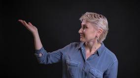 Retrato del primer de la mujer de mediana edad feliz que señala con su mano que presenta un proyecto con la expresión facial aleg almacen de video