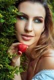 Retrato del primer de la mujer que se sostiene cerca de la fresa dulce roja de la cara Fotografía de archivo libre de regalías