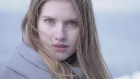 Retrato del primer de la mujer rubia joven hermosa con el pelo largo y los ojos azules que miran en la cámara Mujer atractiva de almacen de video