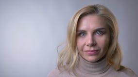 Retrato del primer de la mujer rubia de mediana edad que tienta a la cámara y que aumenta su ceja en fondo gris metrajes
