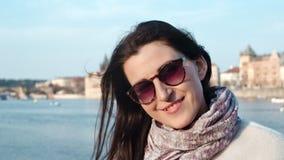 Retrato del primer de la mujer turística sonriente en gafas de sol que disfruta de paisaje urbano en orilla del mar en la puesta almacen de metraje de vídeo