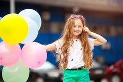 Retrato del primer de la niña en la ropa brillante que juega con los globos Imagen de archivo