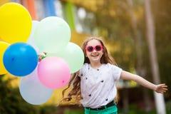 Retrato del primer de la niña en la ropa brillante que juega con los globos Fotos de archivo libres de regalías