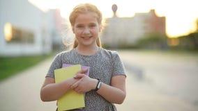 Retrato del primer de la niña europea rubia que sonríe con todos sus dientes El niño feliz por tarde soleada hace cada almacen de metraje de vídeo