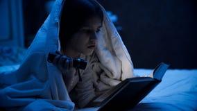 Retrato del primer de la niña que miente en libro de la cama y de lectura con la linterna Imagen de archivo